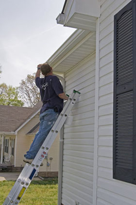 A sydney exterior house painter, painting facia, eves, gutter and cladding.